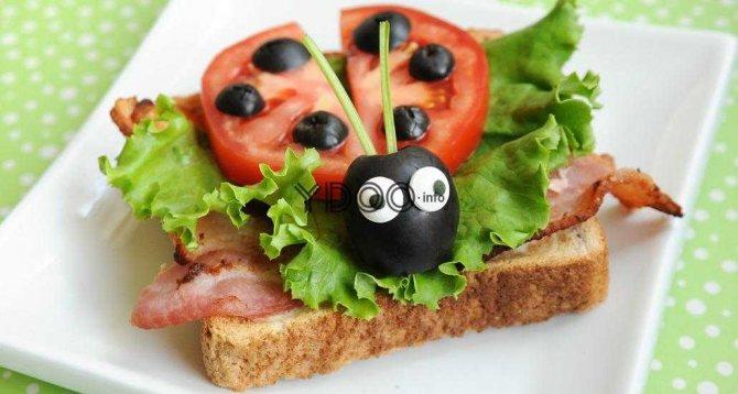 бутерброд з помідором і маслинами в вигляді сонечка